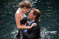 Young couple wearing formalwear embracing in water