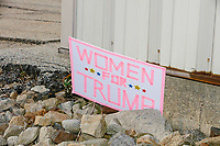 """A handmade sign reading """"Women for Trump"""" is seen among rocks outside a Make America Great Again Victory Rally with US President Donald Trump in the final week before the Nov. 3 election at Pro Star Aviation in Londonderry, New Hampshire, on Sun., Oct. 25, 2020."""