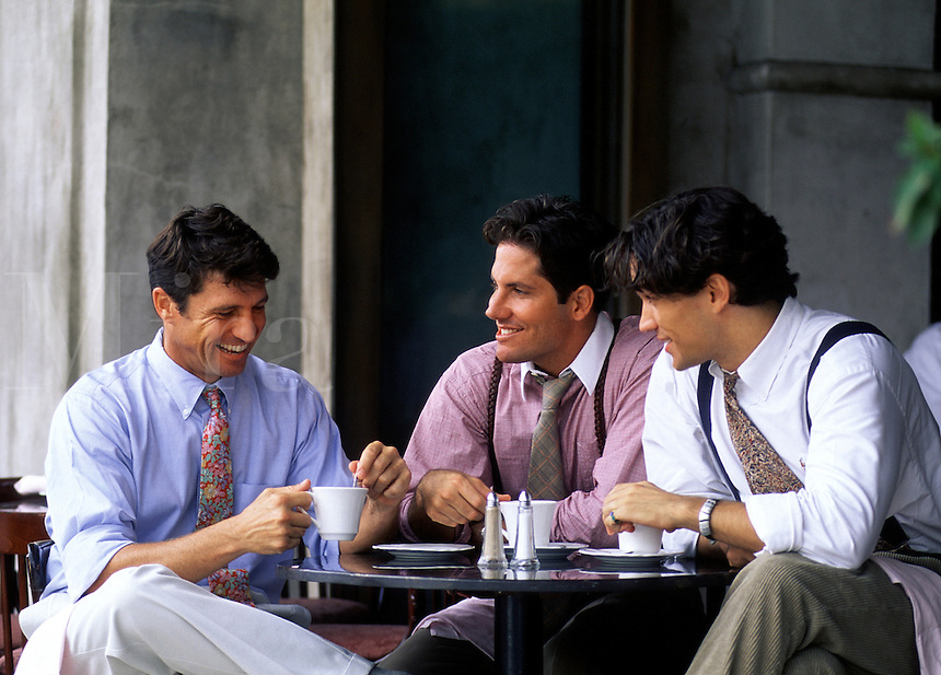 Three smiling young businessmen enjoy having coffee together in a cafe.