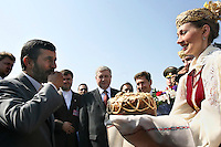 A traditionally dressed Bolrussian woman greets Iranian President Mahmoud Ahmadinejad with cake in the airport of capital Minsk.