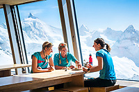 Women sitting inside the Tracuit Hut dining room eating cake and enjoying the panorama view from the big windows. Switzerland.