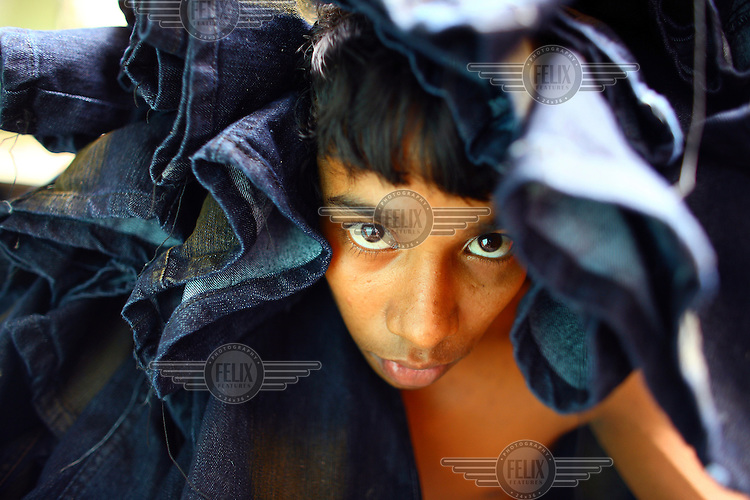 A young man working in a garment factory carries a load of newly made denim jeans.