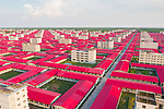 Pictured:  Brightly coloured red rooftops look like they are part of a real life Tetris game spanning an entire city.<br /> <br /> The perfectly aligned buildings, which are reminiscent of the 1980's tile-matching video game, were constructed for displaced Rohingya Muslims from Myanmar.<br /> <br /> The makeshift city, which is currently empty, is large enough to house at least 100,000 refugees.<br /> <br /> The unusual images were captured by photographer and videographer Mominul Islam Momin on the island of Bhasan Char in the Bay of Bengal.  SEE OUR COPY FOR FULL DETAILS.<br /> <br /> Please byline: Mominul Islam Momin/Solent News<br /> <br /> © Mominul Islam Momin/Solent News & Photo Agency<br /> UK +44 (0) 2380 458800