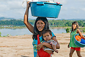 Pará State, Brazil. Aldeia Apyterewa (Parakana). Woman with plastic bowl on her head and child on her arm.