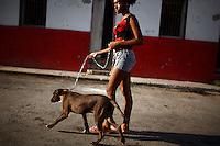 A woman walks a dog through an alley in Havana, Cuba on 10 October 2008.