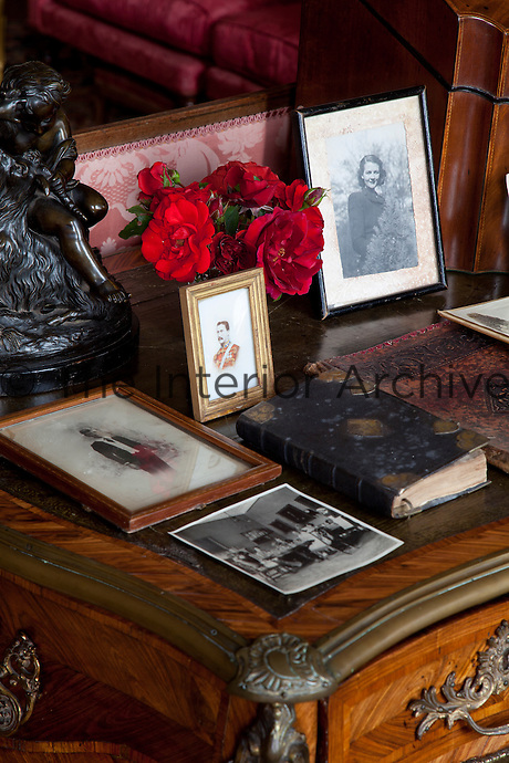 Vintage photographs, books and a miniature adorn an antique desk in the drawing room