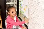 Preschool ages 3-5 portrrait of girl smiling and pointing at name chart horizontal