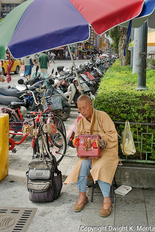 Outside Longshan temple, a Buddhist monk catches a short nap (of nodding meditation) while sitting under an umbrella.