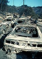 burned automobiles along neighborhood street in Oakland Hills fire of October 1991. burn, burned, fire, hot, insurance, loss, damage, arson, charred, ruins, disaster. Oakland California USA Oakland Fire Oct. '91.