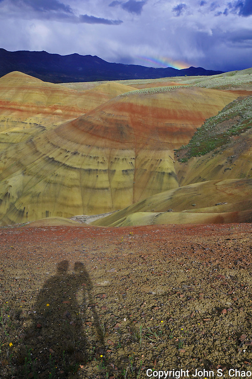 A photographer's shadow is cast before  Painted Hills National Monument with small rainbow behind it in central Oregon.
