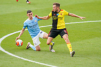 Phil Foden of Man City and Tom Cleverley of Watford during the Premier League match between Watford and Manchester City at Vicarage Road, Watford, England on 21 July 2020. Football Stadiums around remain empty due to the Covid-19 Pandemic as Government social distancing laws prohibit supporters inside venues resulting in all fixtures being played behind closed doors until further notice.<br /> Photo by Andy Rowland.