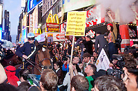 "Police officers threaten protesters with ""Occupy Wall Street"" by advancing on horseback in Times Square on October 15, 2011 in New York City.  While crowd estimates numbered in the tens of thousands, police tactics (including nets, motor scooters, barricades, arrests, and intimidation by riders on horseback) prevented the crowd, which had been split up, from joining together as one in the middle of Times Square."