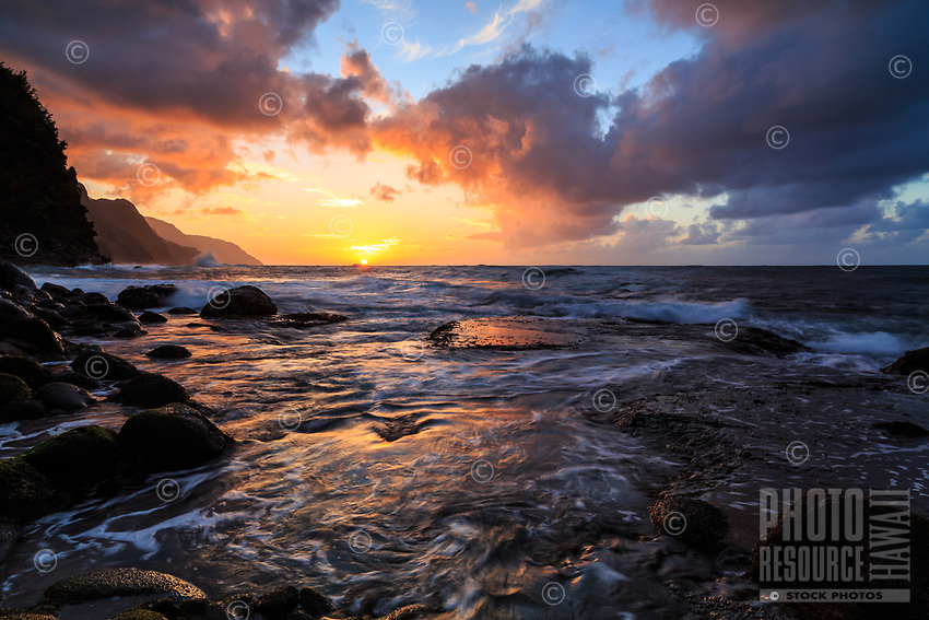 The sun sets on the Na Pali coastline while a dynamic ocean flows over a rocky reef at Ke'e Beach, Kaua'i.