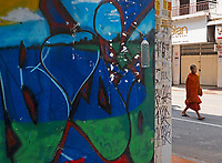In the streets of Phnom Penh, Monl walking past Graffiti, Cambodia