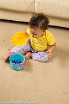 10 month old baby girl searching for and finding toy hidden inside plastic pot with lid