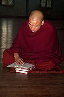 Myanmar, Burma.  Monk Reading Scriptures at Thein Taung Paya monastery, Kalaw, Shan State.