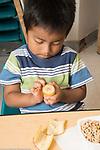 Education Preschool 3-4 year olds boy peeling banana at breakfast time