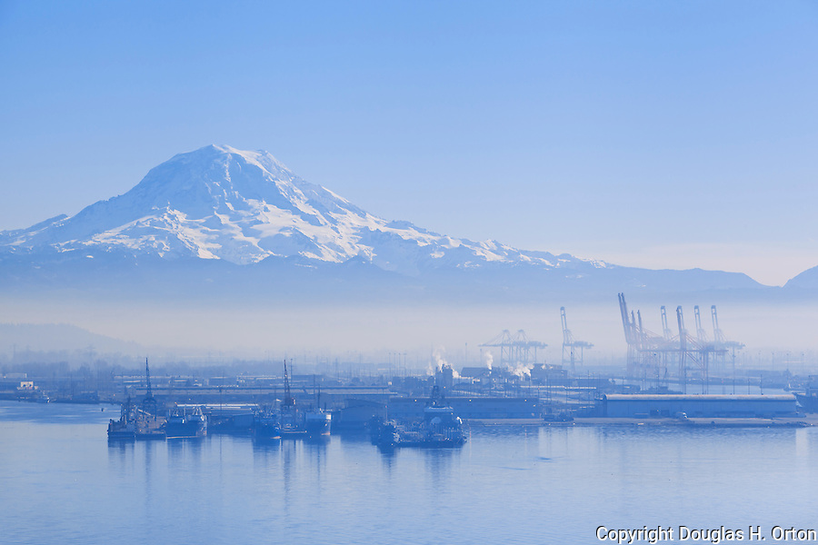 Shrouded in winter smog, once pristine Commencement Bay with Mount Rainier National Park  in the background, supports the industrial base of Tacoma, Wa on tideflats that once formed the delta of the Puyallup River and home of the Puyallup Native American people.  Commencement Bay's history of industry and shipping has led it to designation as a Superfund Cleanup Site and one of the most polluted waterways in the nation.  Commencement Bay Nearshore/Tideflats (CB/NT) Superfund Site.  Please contact the photographer regarding licensing this image.