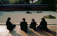 Young Japanese students contemplate the rock garden of Ryoanji temple. Kyoto, Japan.