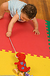 9 month old baby girl pulling string on wheeled toy to move it closer