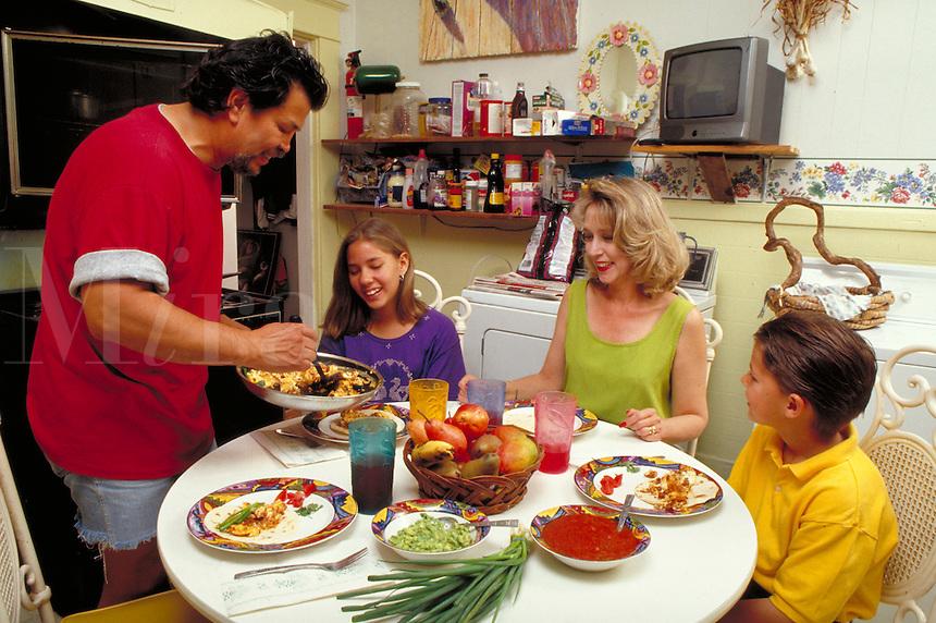 HISPANIC FAMILY EATS BRUNCH IN KITCHEN. CHORIZO AND EGGS. HISPANIC FAMILY. SAN ANTONIO TEXAS.
