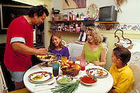 HISPANIC FAMILY EATS BRUNCH IN KITCHEN. CHORIZO AND EGGS. HISPANIC FAMILY. SAN ANTONIO TEXAS.