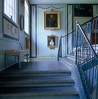 Gilt-framed ancestoral portraits hang on the walls of this double staircase