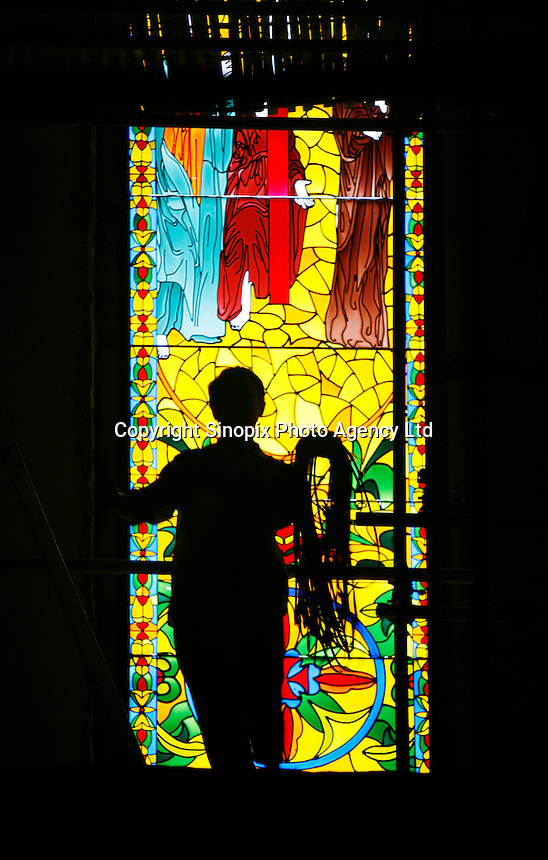 """A worker carrying ropes passes in front of a stained-glass window at a mock chapel being built in Thames Town, in Shanghai, China. Thames Town is one of several satellite townships that Shanghai is building in hopes of luring residents away from the city centre, and claims to allow people to """"taste authentic British style of small town""""..21 Jul 2006"""