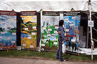 A woman looks at a poster display with information about climate change outside the tent filled with displays of research focusing on clean energy and sustainable living in Eastman Court during the MIT Under the Dome open house in Cambridge, Massachusetts, USA.
