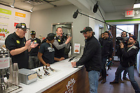 """Morgan Spurlock applauds the first customer at the opening of  """"Holy Chicken,"""" a faux fast food restaurant in Columbus, Ohio, where a documentary crew recorded his interaction with customers who thought they were dining at a new type of fast food restaurant. However, the entire location was designed to be part of his documentary highlighting the marketing of food that may not be as healthy as it is stated in advertisement, banners, and notices at the restaurant."""