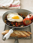 Small frying pan with sunny-side up fried egg and tomato halves and pesto, on top of stewed black beans, peppers, and onions. Grilled bread slice on the side
