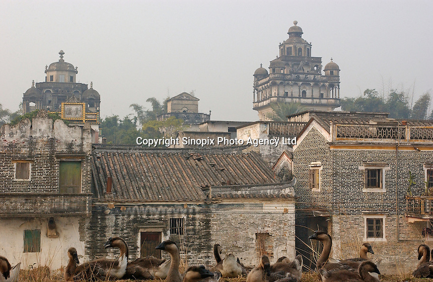 """A European """"tower"""" in Jin Jiang Li dwarfs traditional houses in this town near Kaiping city in Guangdong Province, China. The European style """"towers"""" were built by  .overseas Chinese returning with architectural ideas from America and Europe. The area is .one of the World Heritage Site.."""