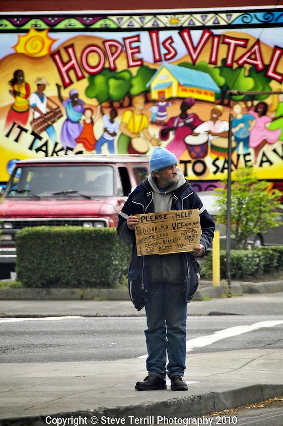 USA, Oregon, Homeless man on street corner holding sign at passing cars in Portland
