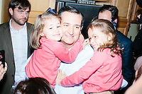 """Campaign staffers look on while Texas senator and Republican presidential candidate Ted Cruz holds his two daughters Catherine (left) and Caroline after speaking at an event called """"Smoke a cigar with Ted Cruz"""" at a house party at the home of Linda & Steven Goddu Salem, New Hampshire. Cruz briefly smoked a cigar after speaking at the event."""