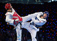 05 MAY 2012 - MANCHESTER, GBR - Aaron Cook (GBR) of Great Britain (right in blue) tries to evade a kick from Ramin Azizov (left in red) of Azerbaijan during the men's 2012 European Taekwondo Championships -80kg final at Sportcity in Manchester, Great Britain (PHOTO (C) 2012 NIGEL FARROW)
