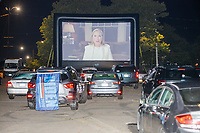 """Former Democratic nominee for President Hillary Clinton is seen on a screen as people gathered to watch the 2020 Democratic National Convention at a """"Ridin' with Biden"""" Drive-In Theater viewing event at Suffolk Downs in Boston, Massachusetts, on Wed., Aug. 19, 2020."""