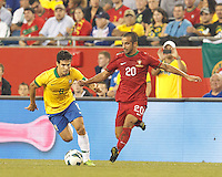 Portugal substitute midfielder Ruben Amorim (20) passes as Brazil substitute midfielder Hernanes (8) closes. In an international friendly, Brazil (yellow/blue) defeated Portugal (red), 3-1, at Gillette Stadium on September 10, 2013.