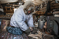 Ion Maxsimovic prepares kindling for the wood stove in his winter hunting lodge. He will get up numerous times in the night to keep the fire burning as temperatures in the region can get as low as minus 50 degrees celsius, cold enough to freeze a carcass solid in less than two hours.