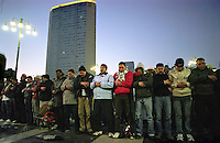 Milano, manifestazione contro l'attacco di Israele alla Striscia di Gaza. Manifestanti in preghiera sul piazzale della Stazione Centrale con alle spalle il grattacielo pirelli --- Milan, demonstration against the attack of Israel to the Gaza Strip. Demonstrators praying on the square of the central station with the Pirelli skyscraper behind