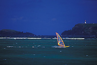 Sail boarder wind surfing in clear lagoon waters off Anini Beach, Kilauea Lighthouse in background, Kauai