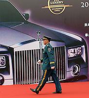 A security guard walks pass an billboard of Guanzhou Luxury Goods Fair in China.