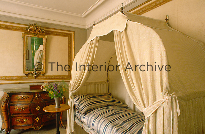 A canopy day bed in a corner of a small panelled bedroom