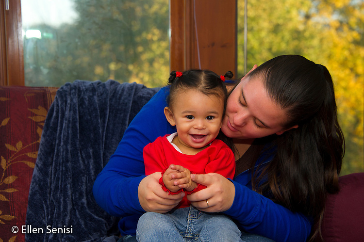 MR / Schenectady, NY. Mother (21) shows her infant daughter (11 months, African American & Caucasian) how to clap hands. MR: Dal4, Dal6. ID: AL-HD. © Ellen B. Senisi
