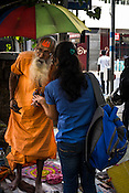 A palmist speaks to a young woman in his road side stall in Kolkata, West Bengal, India,
