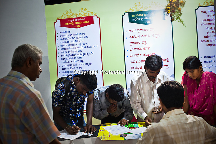 Residents enquire about the Unique Identity (UID) programme and fill up the forms during the national identity enrollment process in Mysore city in Karnataka. Photograph: Sanjit Das/Panos