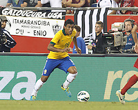Brazil midfielder Paulinho (18) dribbles down the wing.  In an international friendly, Brazil (yellow/blue) defeated Portugal (red), 3-1, at Gillette Stadium on September 10, 2013.