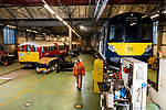 Pictured: Kieren Hetherington, a maintenance fitter for South West Trains walks through the workshop at Ryde St Johns Road train station, Isle of Wight with the old British Rail Class 483 Island Line train (left) after its last passenger service on Sunday 3rd January 2021, ahead of being delivered to the Isle of Wight Steam Railway as the line prepares to unveil a new fleet of London Underground trains in the spring, the new British Rail Class 484 (right).<br /> <br /> The trains, which previously served the London Underground's Northern Line are estimated to have travelled over 3 million miles in their 82 years of service. The Island Line is currently undergoing 3 months of refurbishment ahead of unveiling a new fleet of trains, five British Rail Class 484, extensively refurbished by Vivarail.<br /> <br /> The previous two fleet service will see the train (pictured) being delivered to the Isle of Wight Steam Railway, and the other to the London Traction Transport Group with the intention of running it on the Epping Ongar Railway.<br /> <br /> In keeping with Island Line's traditions, the Class 484 trains are former London Underground trains which served on the District Line and will modernise the service on the island.<br /> <br /> © Jordan Pettitt/Solent News & Photo Agency<br /> UK +44 (0) 2380 458800