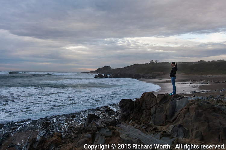 Kacie stands on a rocky outcrop and gazes out at the Pacific Ocean and the incoming waves.