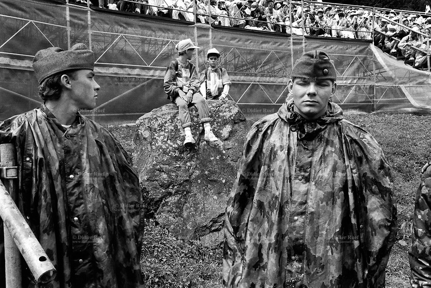 Switzerland. Canton Uri. Rütli 1 August 1991. Swiss national holiday. Public holiday. Two bored soldiers wearing military camouflage uniforms and raincoats stand close to two young boys dressed with sweaters with swiss flag. Rütli (or Grütli in French) is a mountain meadow in the Seelisberg municipality of the Swiss canton of Uri. Here the oath of the Rütlischwur is said to have occurred, the legendary turning-point in the pursuit of independence. Every August 1, on the Swiss National Day, the oath is re-enacted to commemorate the forming of the Old Swiss Confederacy. Rütli is the birthplace of the Swiss Confederation. 1.08.1991 © 1991 Didier Ruef