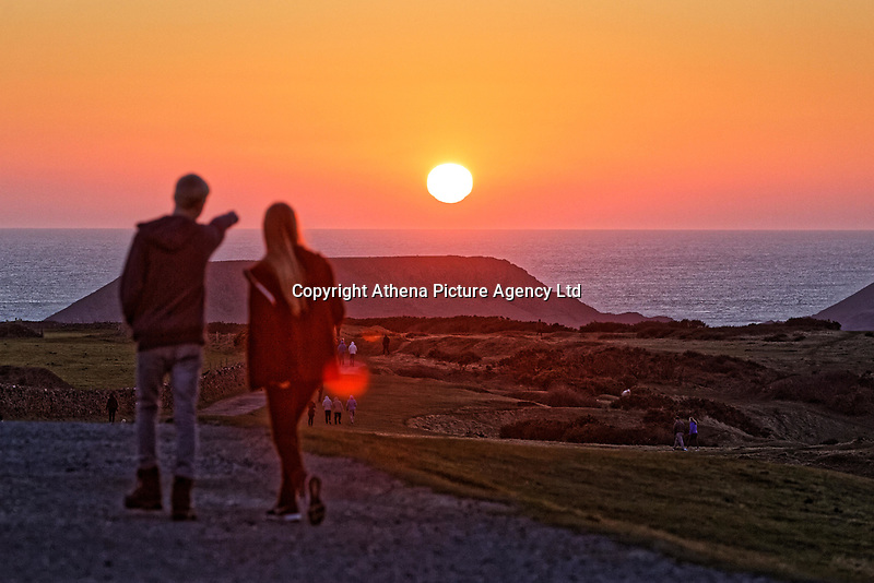 WEATHER PICTURE WALES<br /> Walkers stroll on the path to watch the sun setting over Worms Head near the picturesque village of Rhossili, located in the Gower Peninsula, Wales, UK. Sunday 25 February 2018